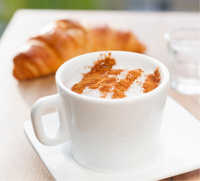Coffee in a white mug dusted with cinnamon, in the background in a croissant