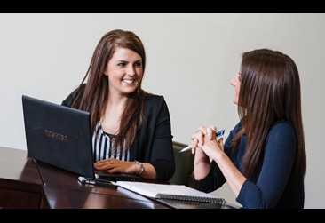 Two women at a desk with a laptop and notepad having a discussion