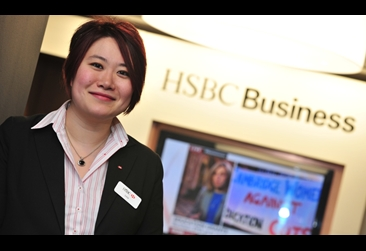 Woman smiling at camera in front of a bank