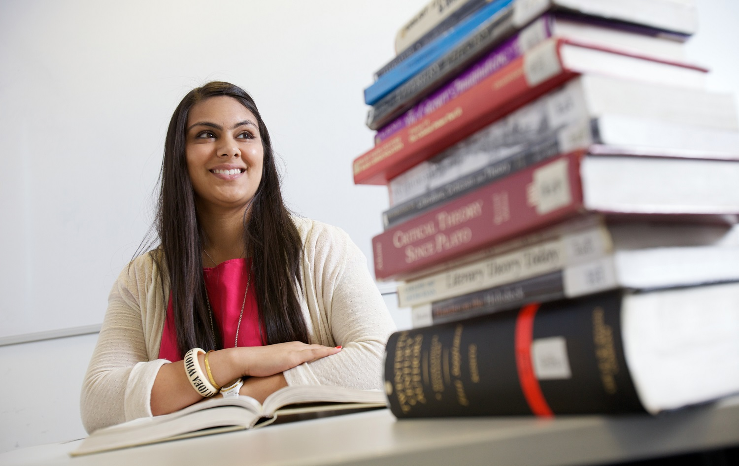 Woman with pile of text books