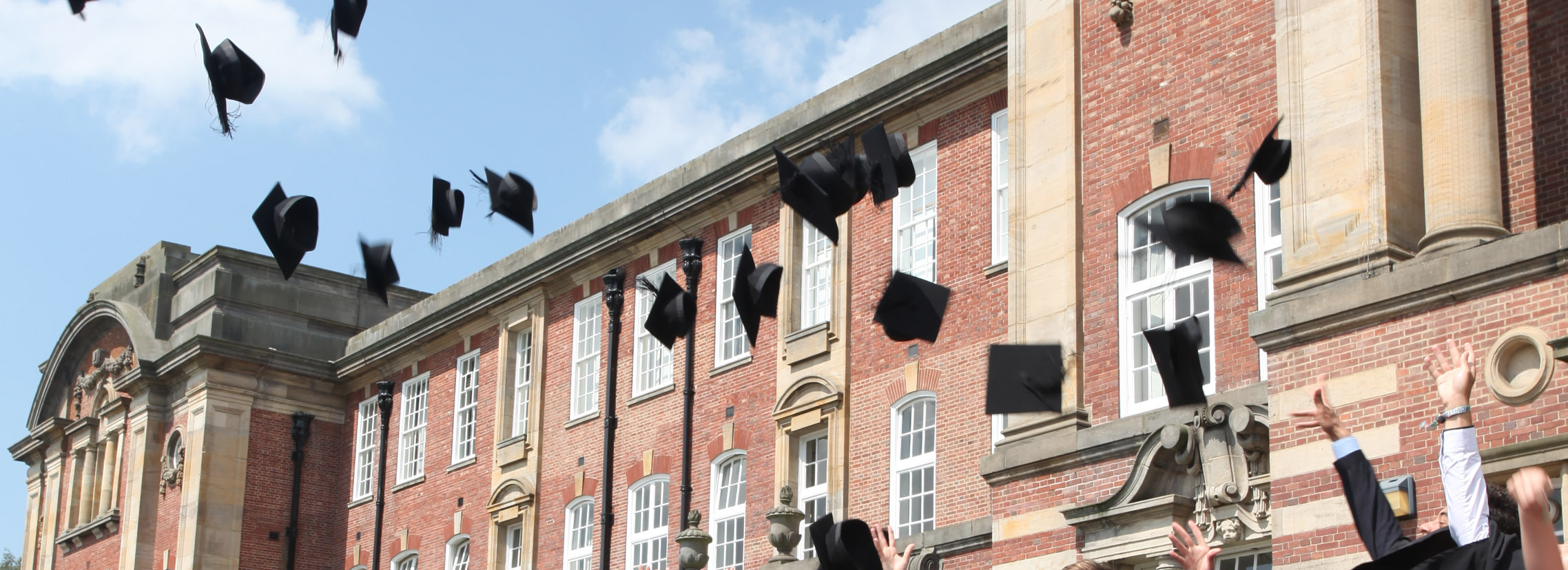 Students throwing their graduation hats into the sky