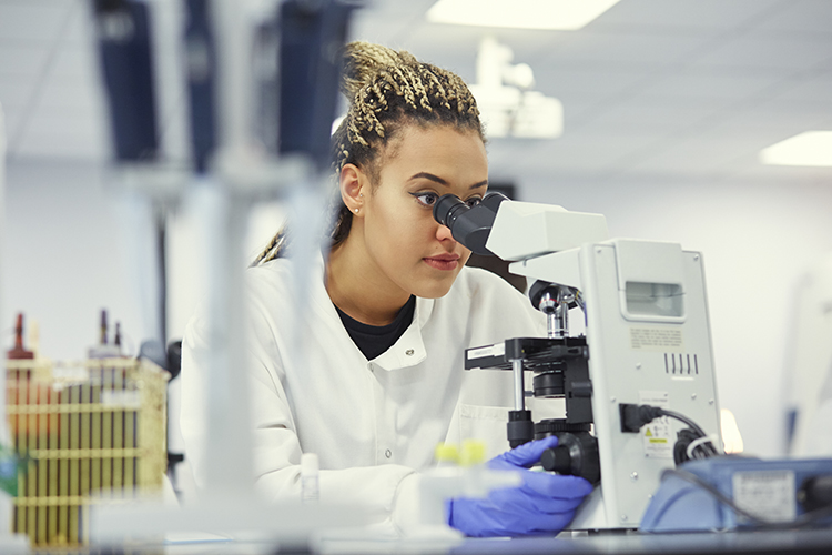 Girl in lab with lab coat on looking through a microscope
