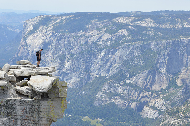 Man stands on the edge of a cliff looking at the scenery