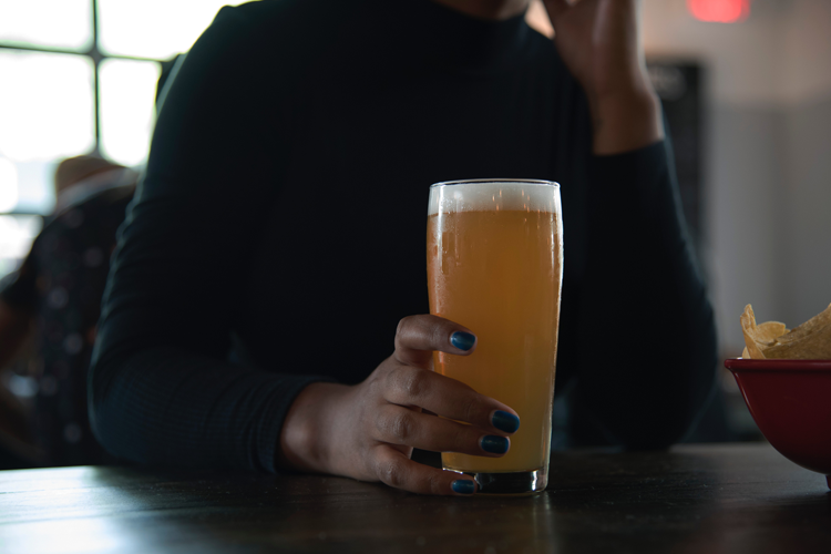 Woman in pub with pint