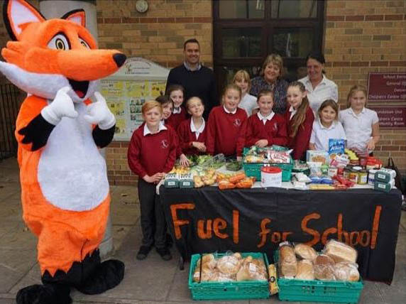 Fred the Fox with school children at a market stall