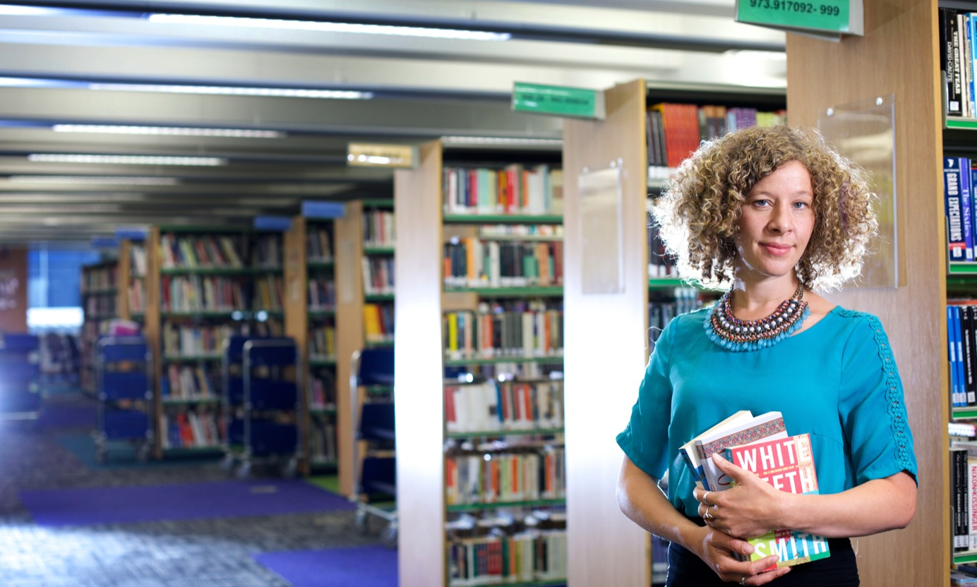 woman stood in a library holding books