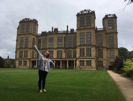 Research student, Catherine Goddard standing in front of a stately home