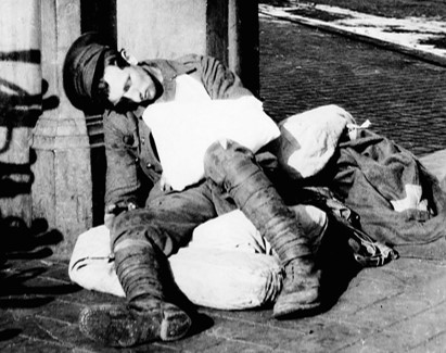 WW1 soldier slumped against a wall
