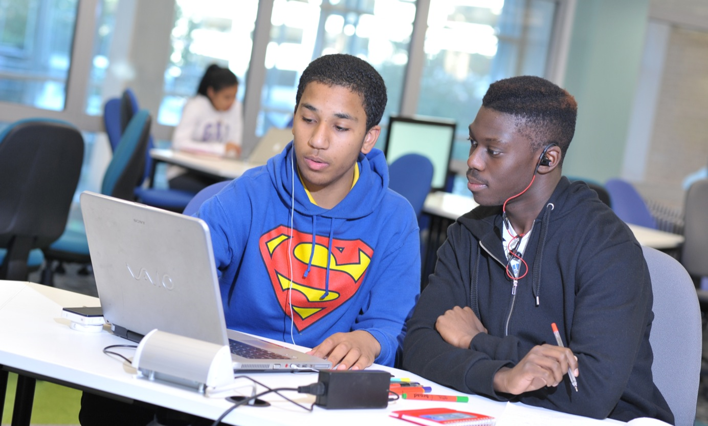 Two students working at a laptop in the library