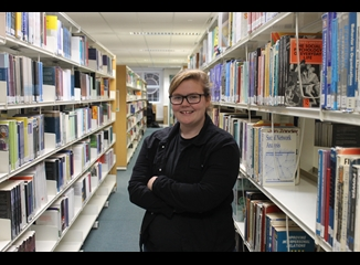 Woman posing amongst bookshelves