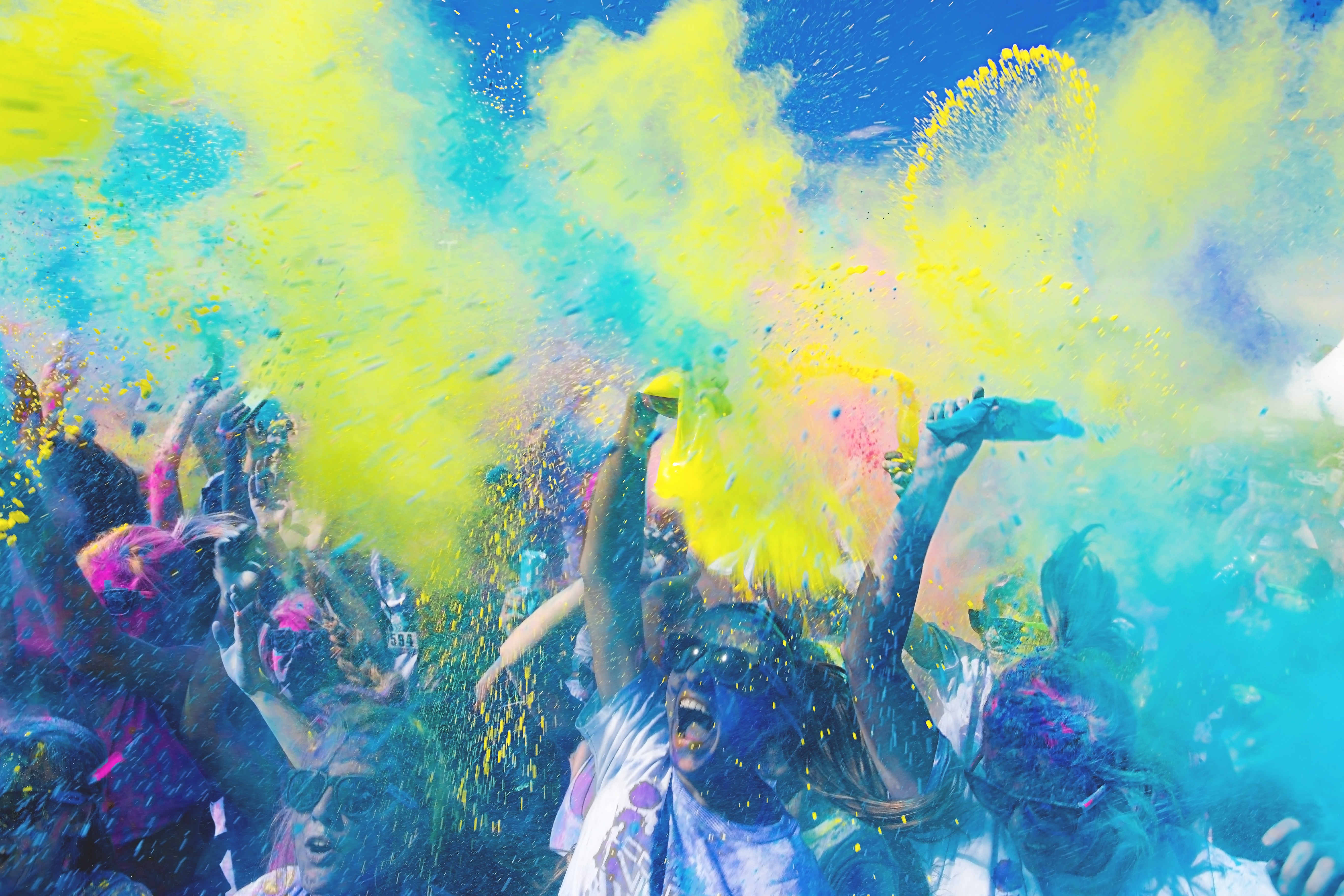 People covered in cloud of colour paint