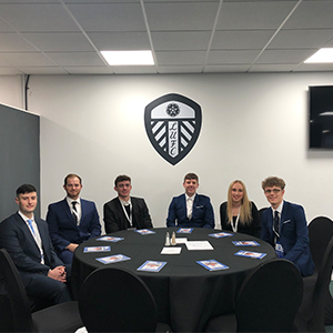 Four students sat round circular table in front of Leeds United logo