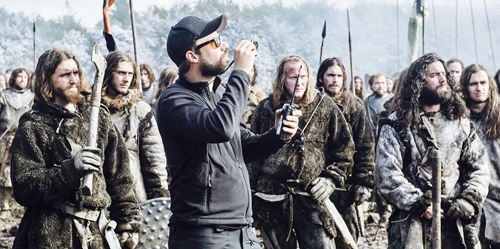 Man in cap holding radio in front of Game of Thrones characters