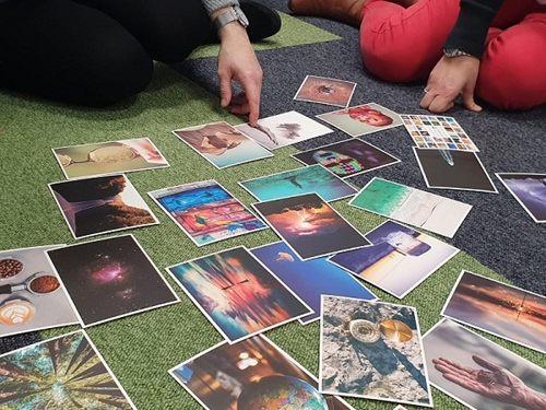 A selection of photos on a green floor, a hand can be seen pointing at one
