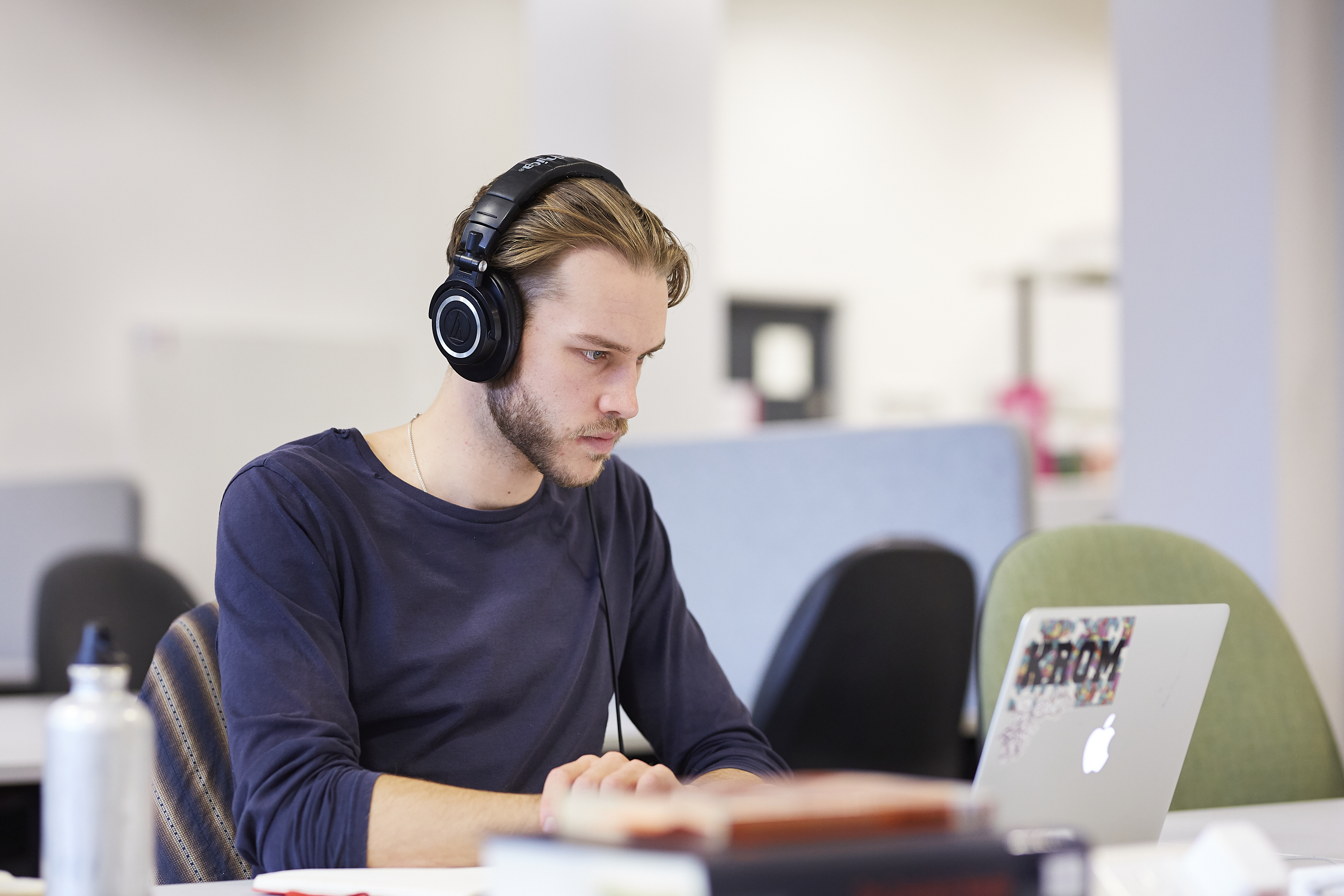 Young man in the Library wearing headphones and looking at a laptop