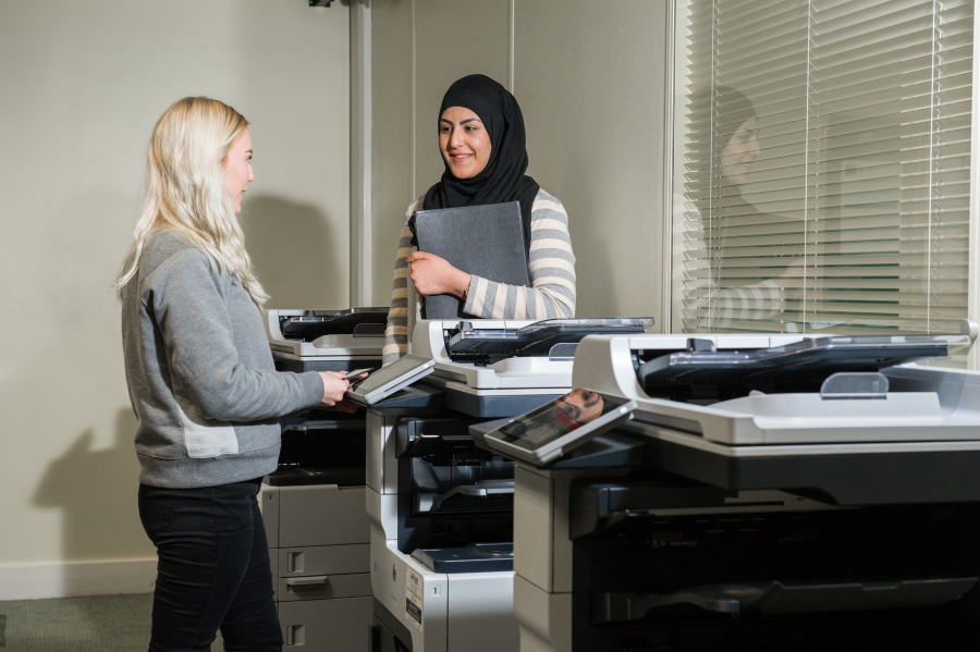 Students in library photocopying