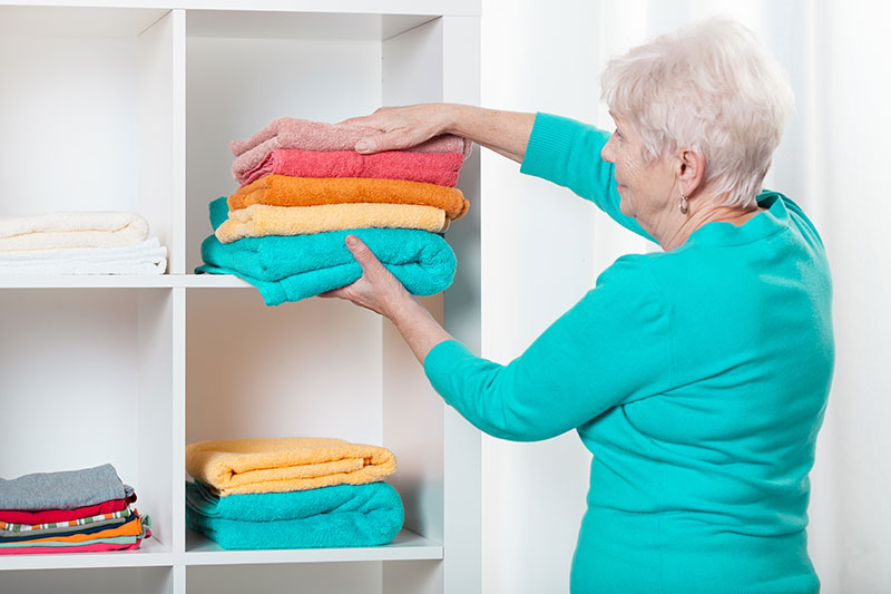A woman putting towels in a cupboard