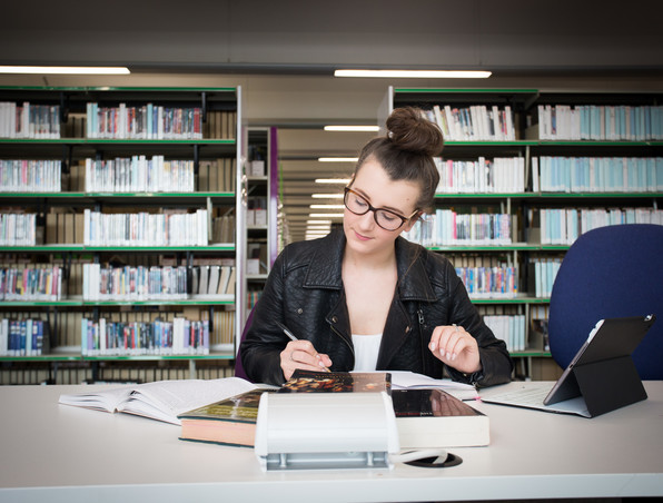 Image of a student studing in a Library
