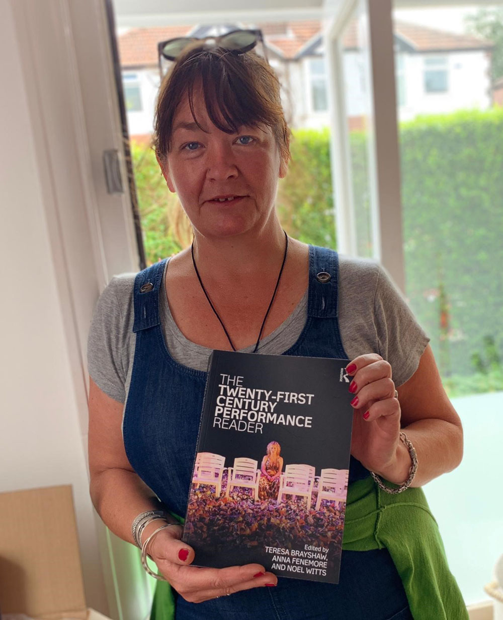 Teresa Brayshaw holding a copy of The 21st Century Performance Reader