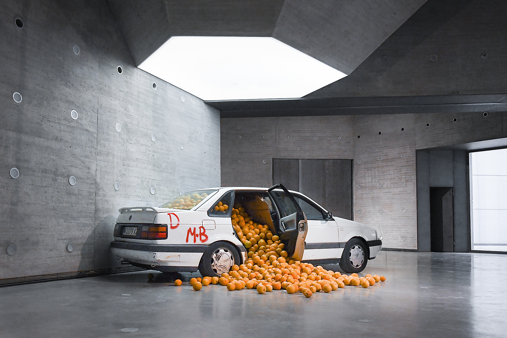 A crashed car with graffitt on it, back door open with oranges coming out, in a gallery