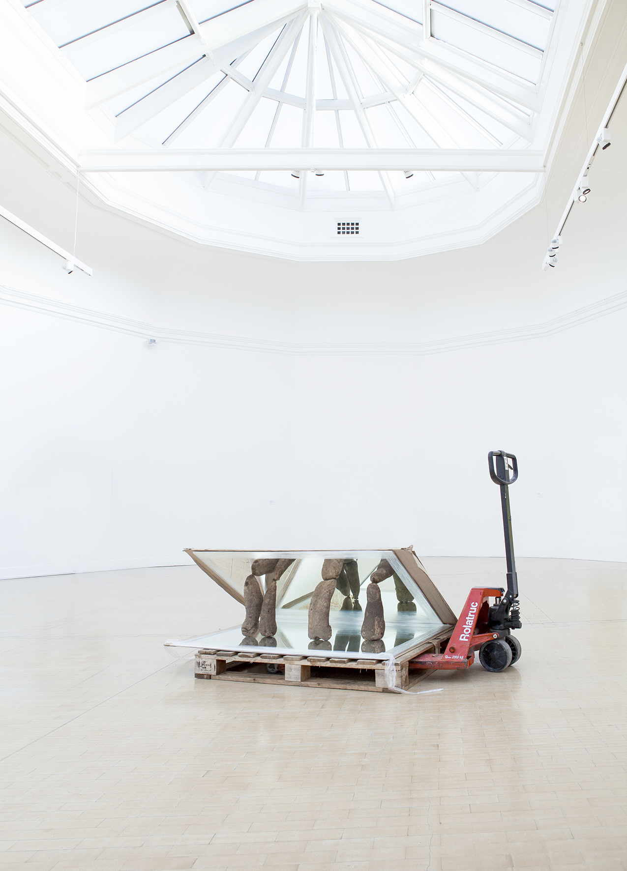 Warehouse trolley, with a mirror and wood on it in the middle of a gallery space