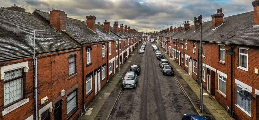 An empty terraced street, lined with parked cars.