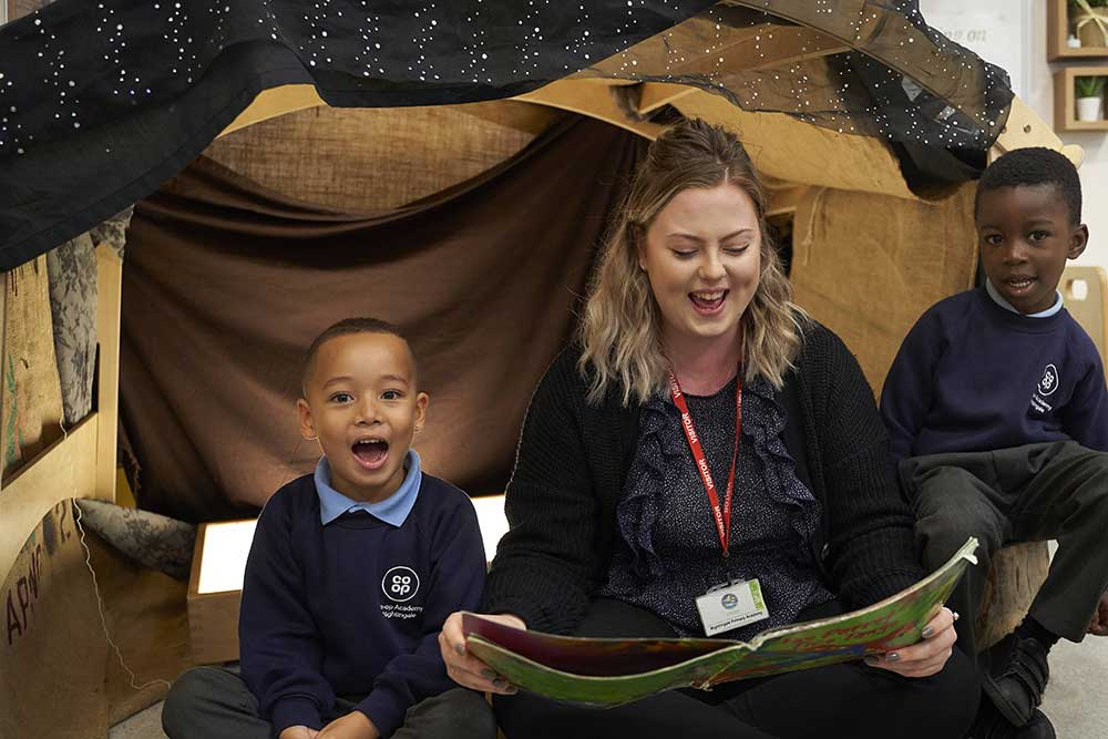 teacher reads to two children in creative play area
