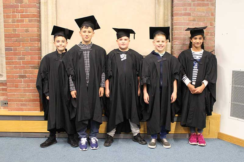Story makers festival, children graduating in hats and gowns