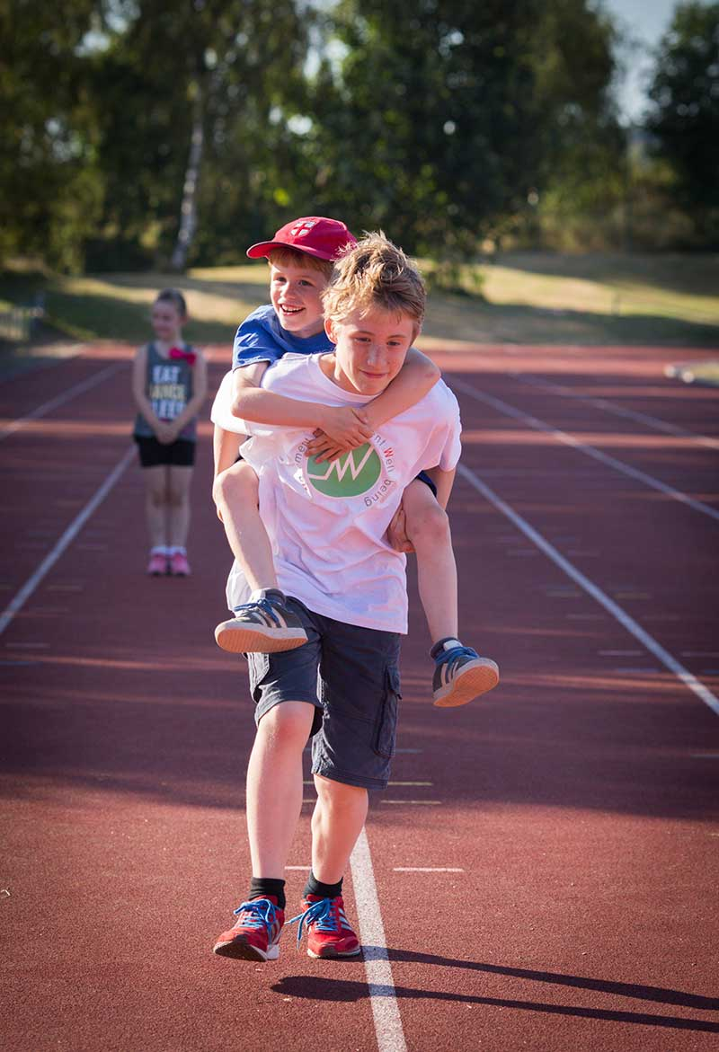 child giving another a child a piggy back ride on a running track