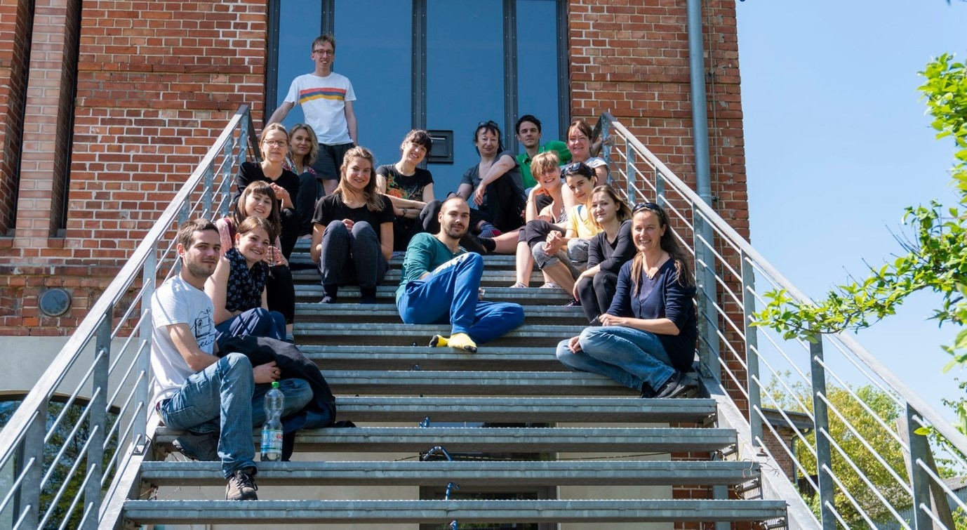 Group of people sat on stairs outside studio