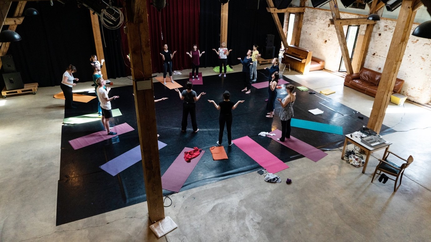 People stood on yoga mats in a circle in studio