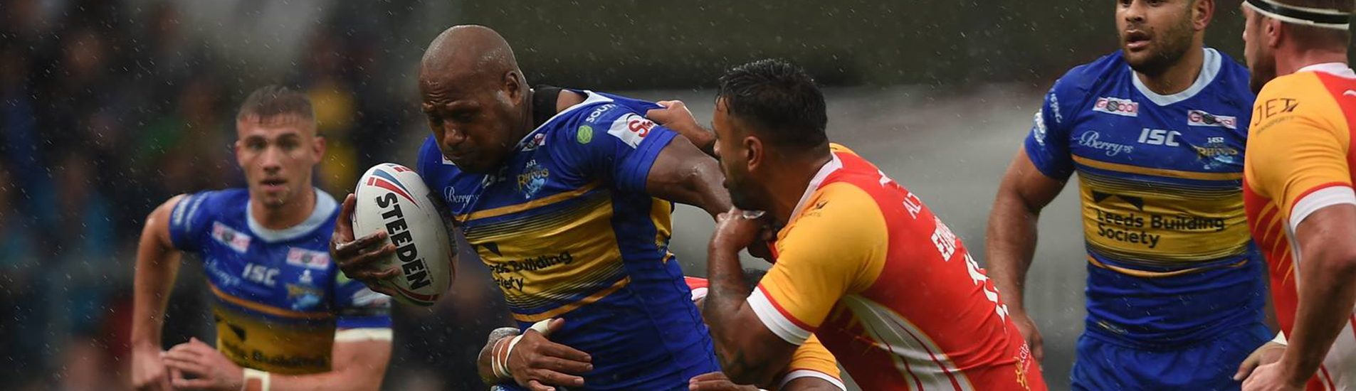 Leeds Rhinos match, player being tackled in the pouring rain