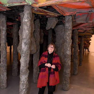 Phyllida Barlow standing inside her art exhibition