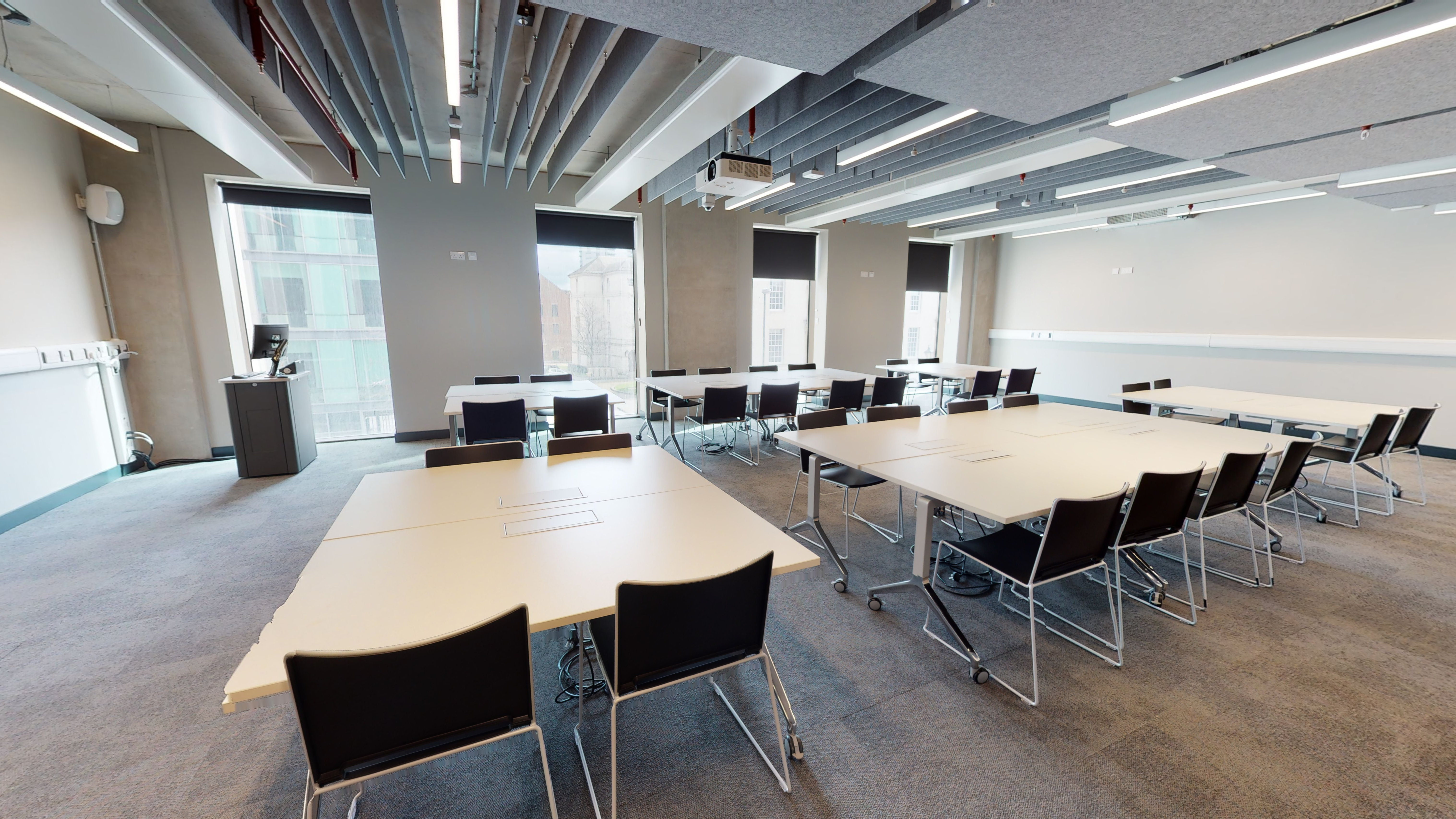 Modern industrial classroom space with tables and chairs