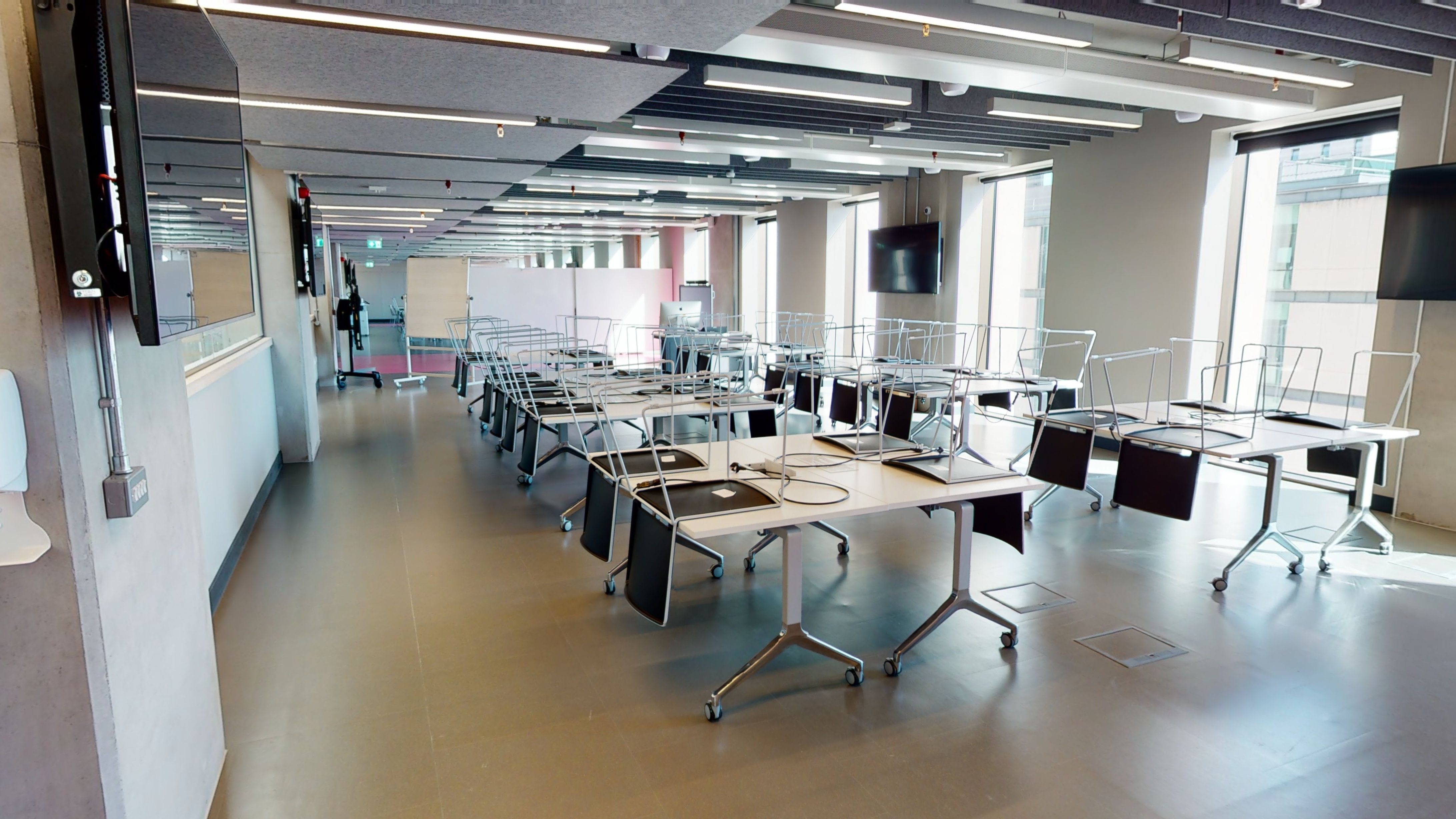 Open modern industrial style classroom/studio space with tables and chairs