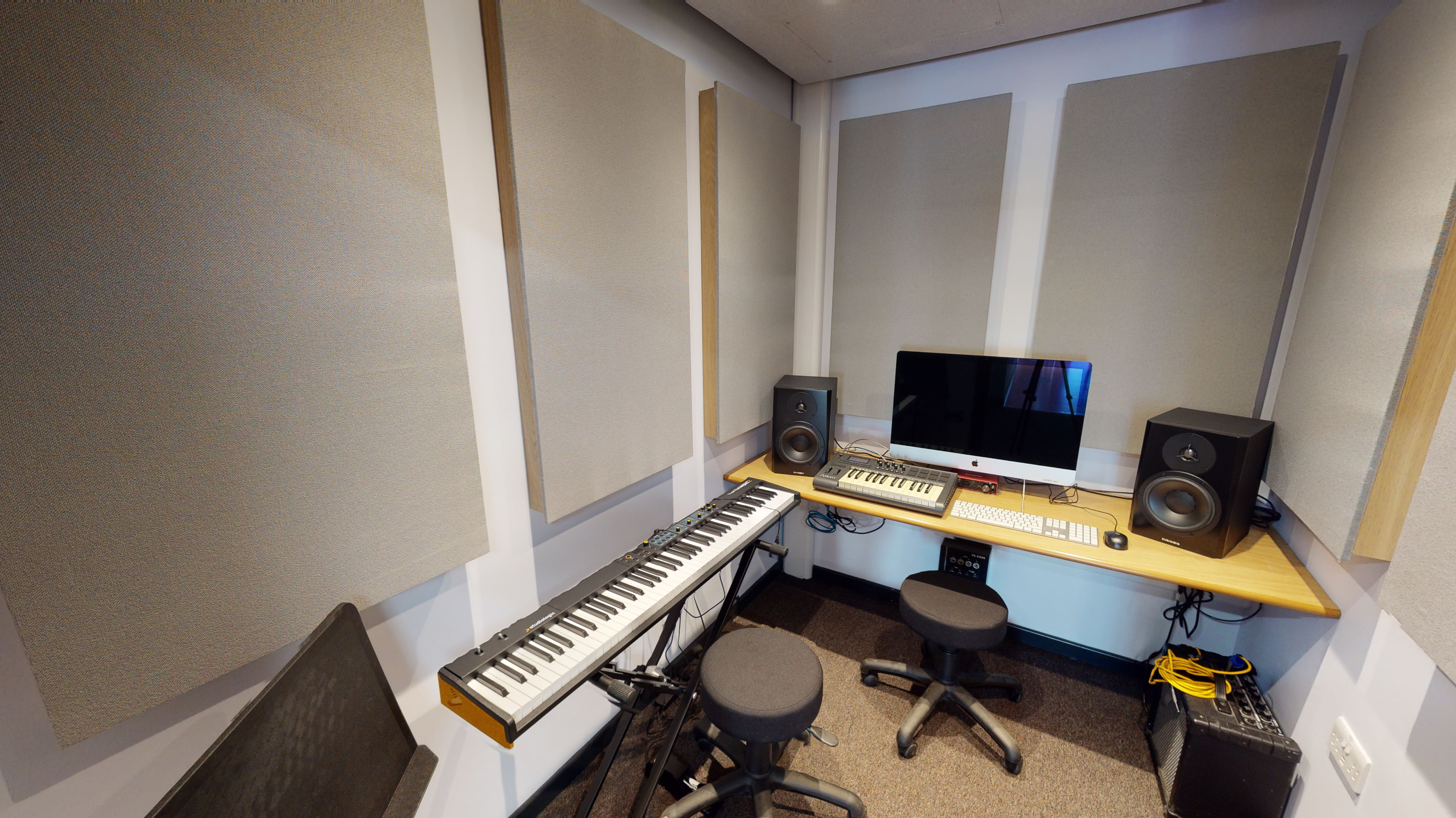 Small insulated room with music keyboard, speakers and computer/ moniotr.