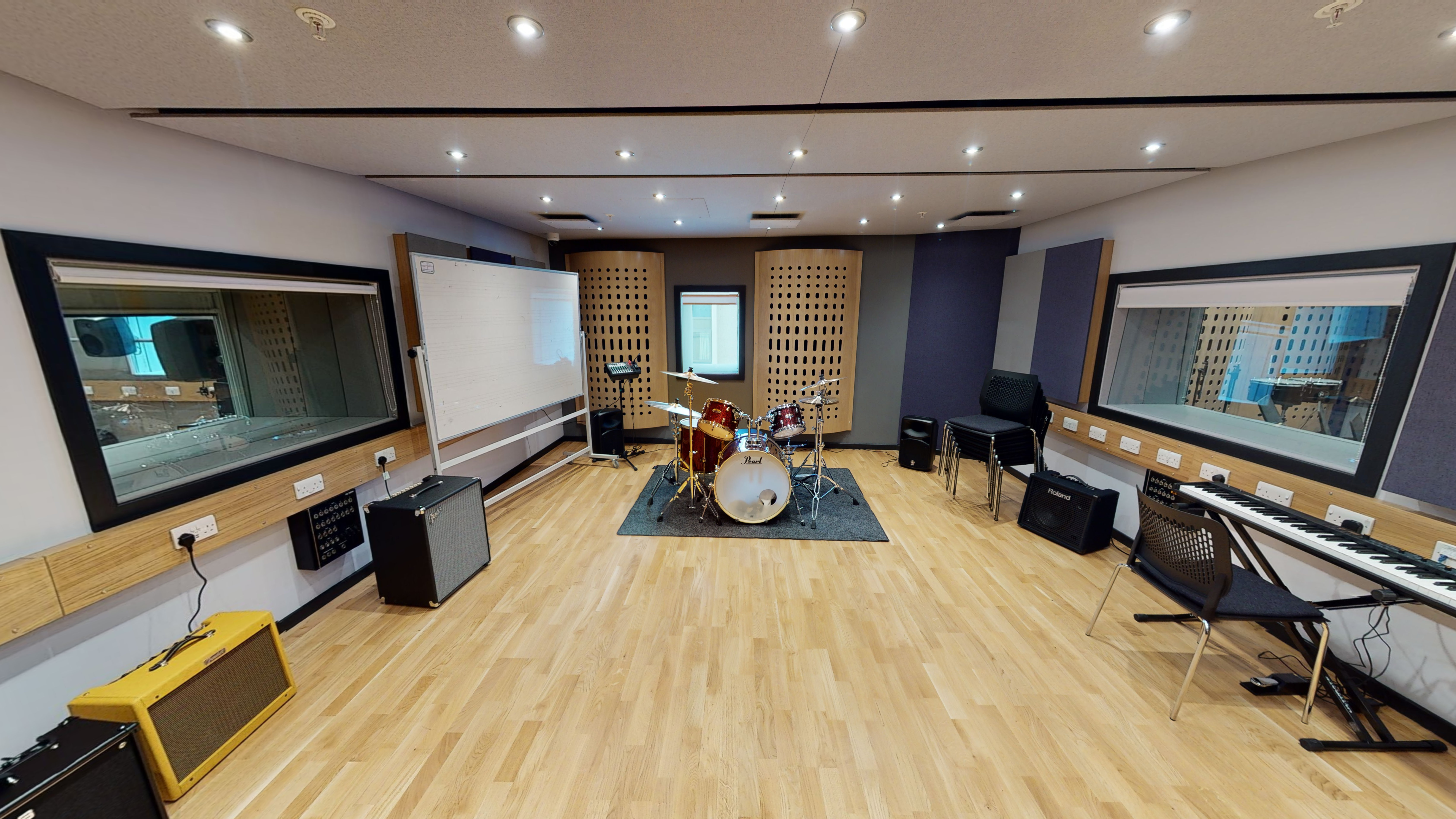 Open music studio space with wooden floor, speakers, amps and control consoles.