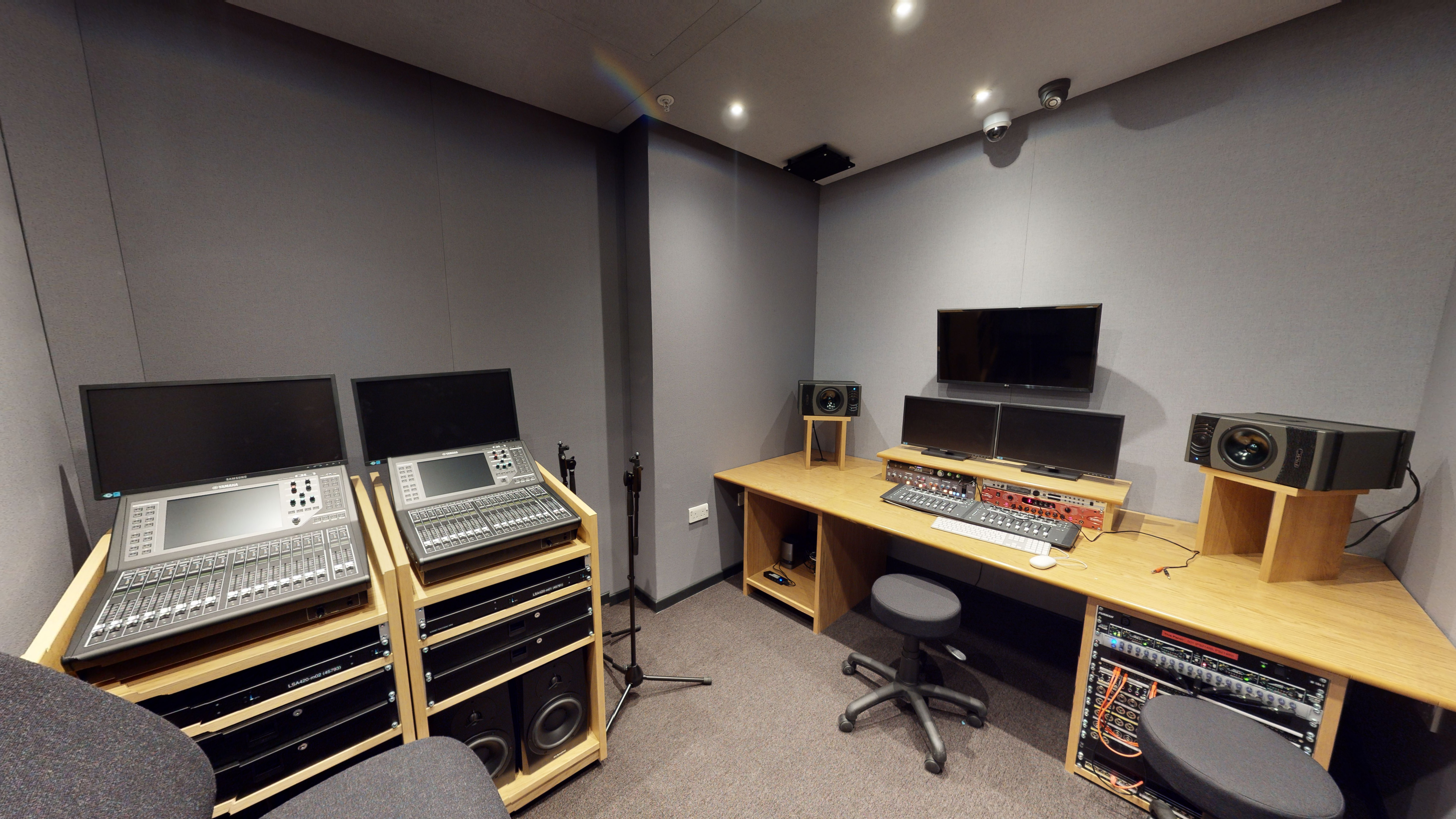Room with a mix of production consoles, computers and speakers set on wooden desks.