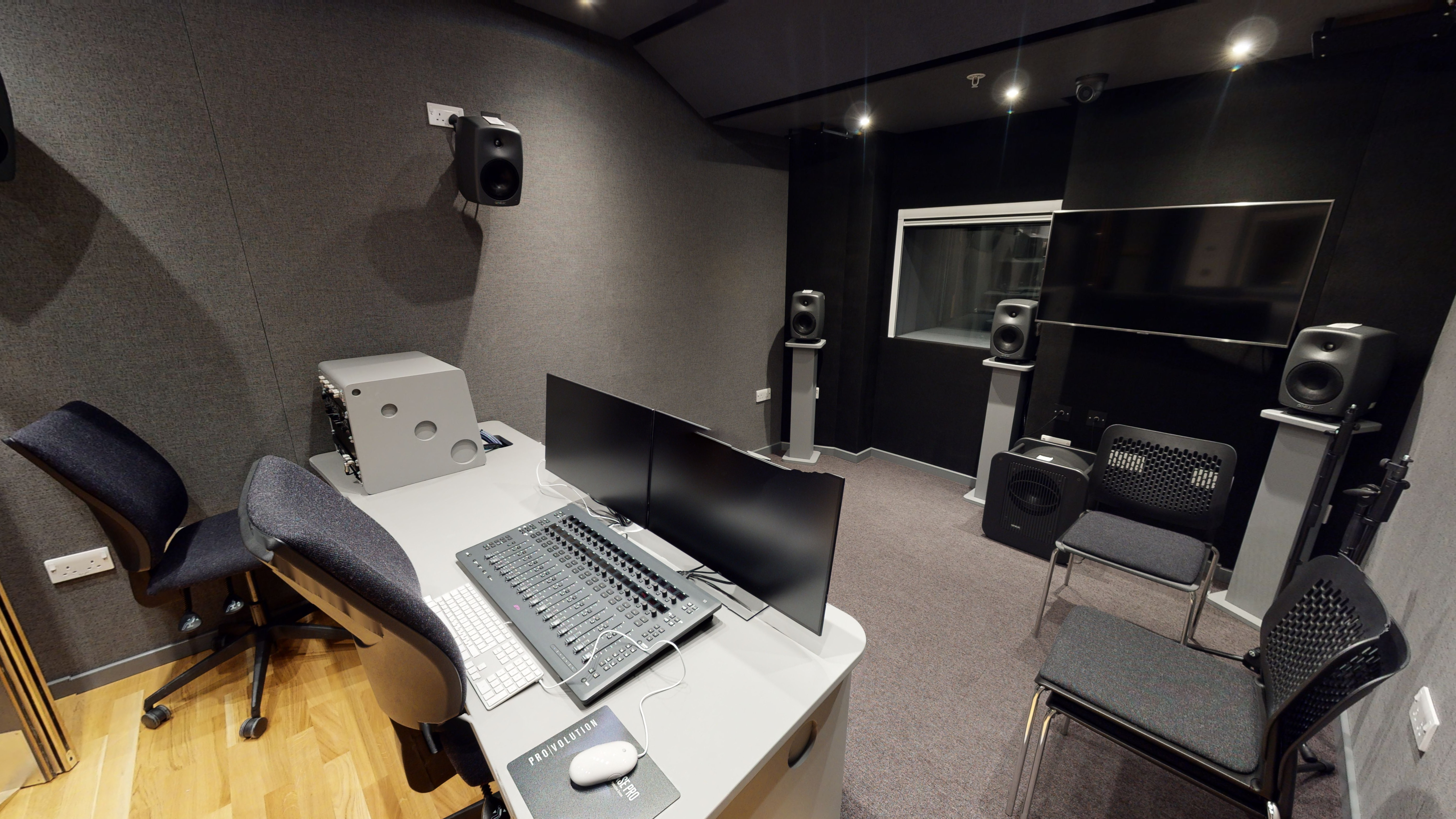 A control desk, with screens, speakers and a seating area in front of it.