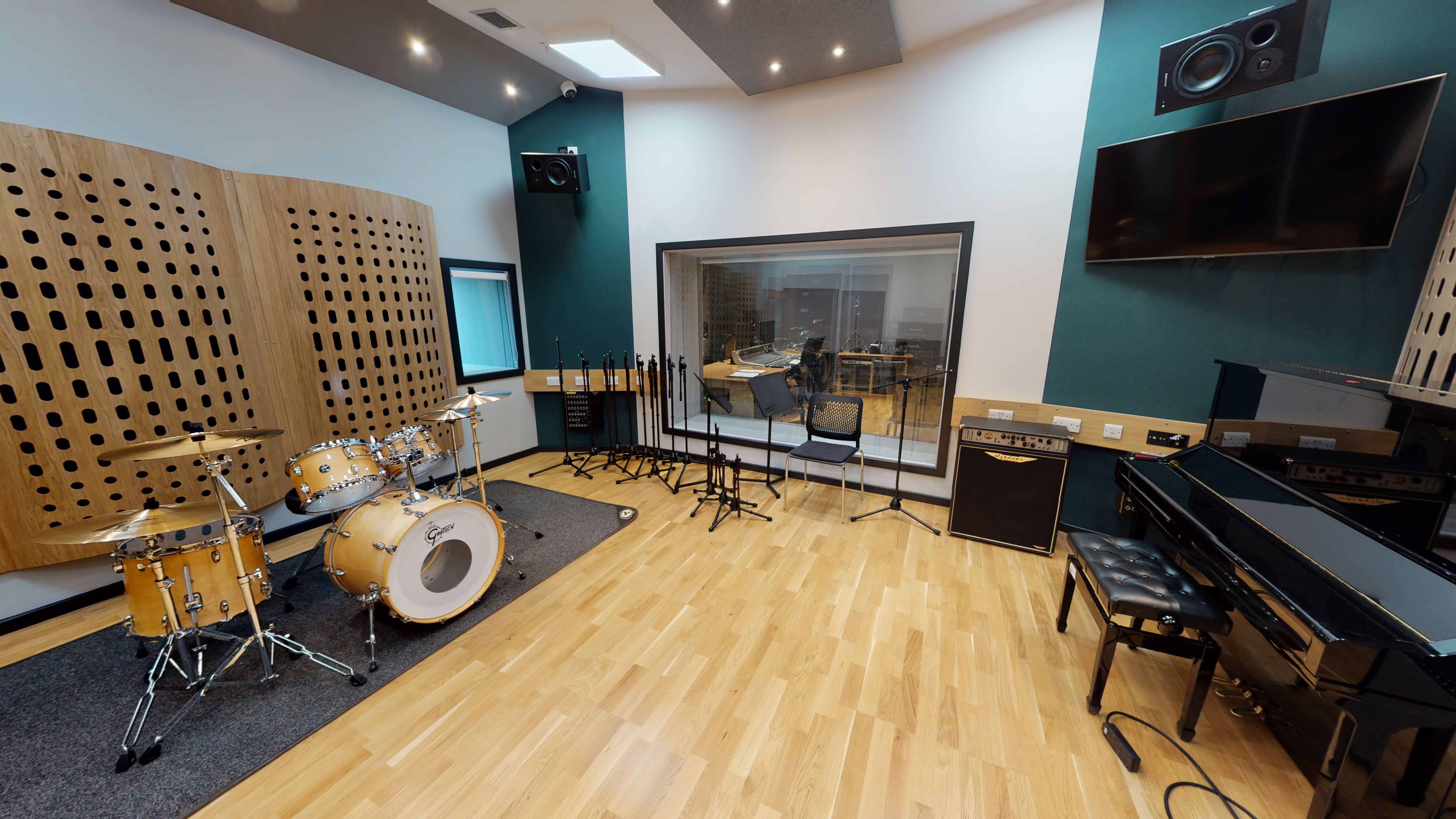 Music studio with large glass window, drums and piano
