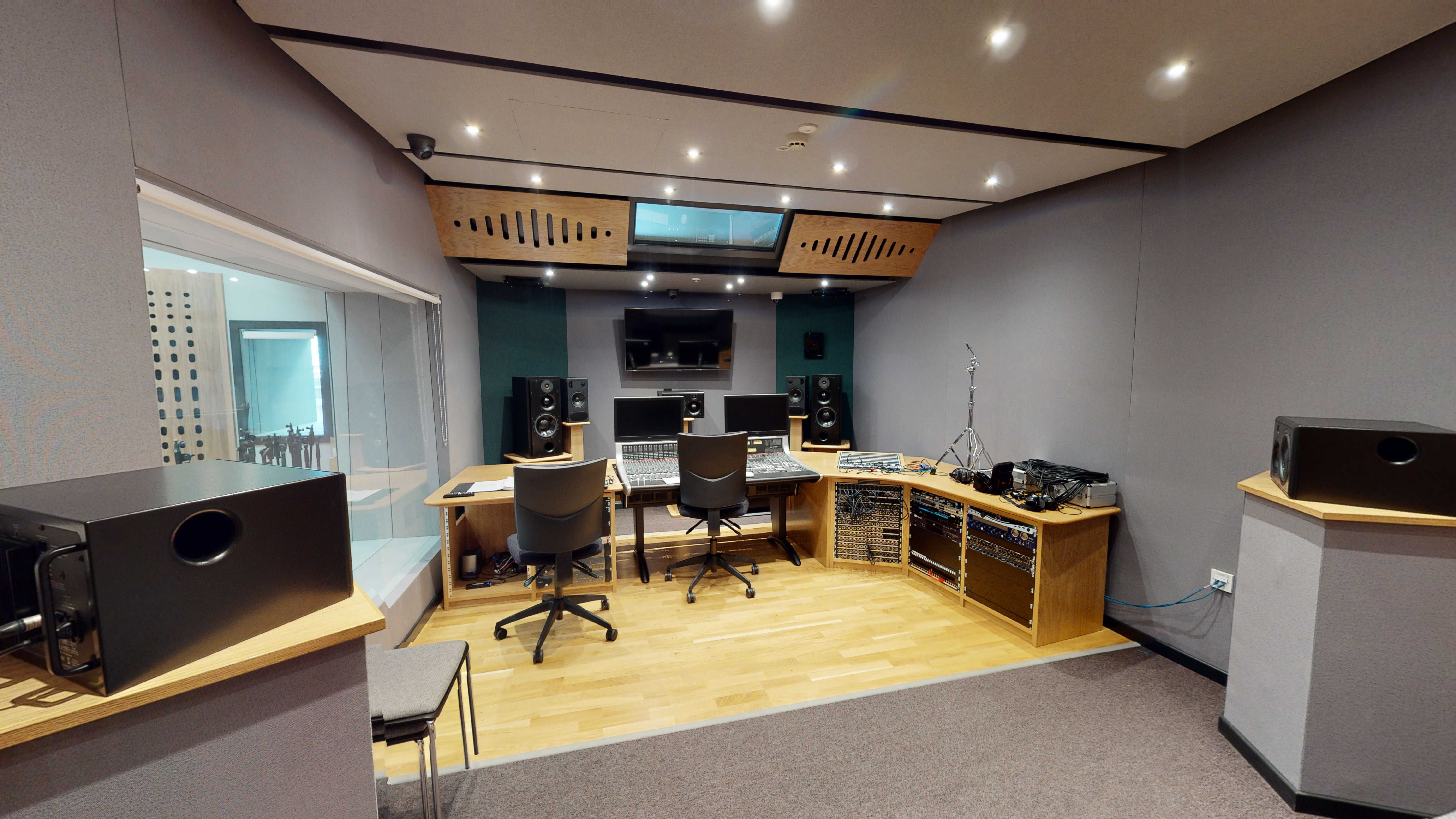 Control room with large window looking into live room/ studio, with large control console, monitors and chairs.