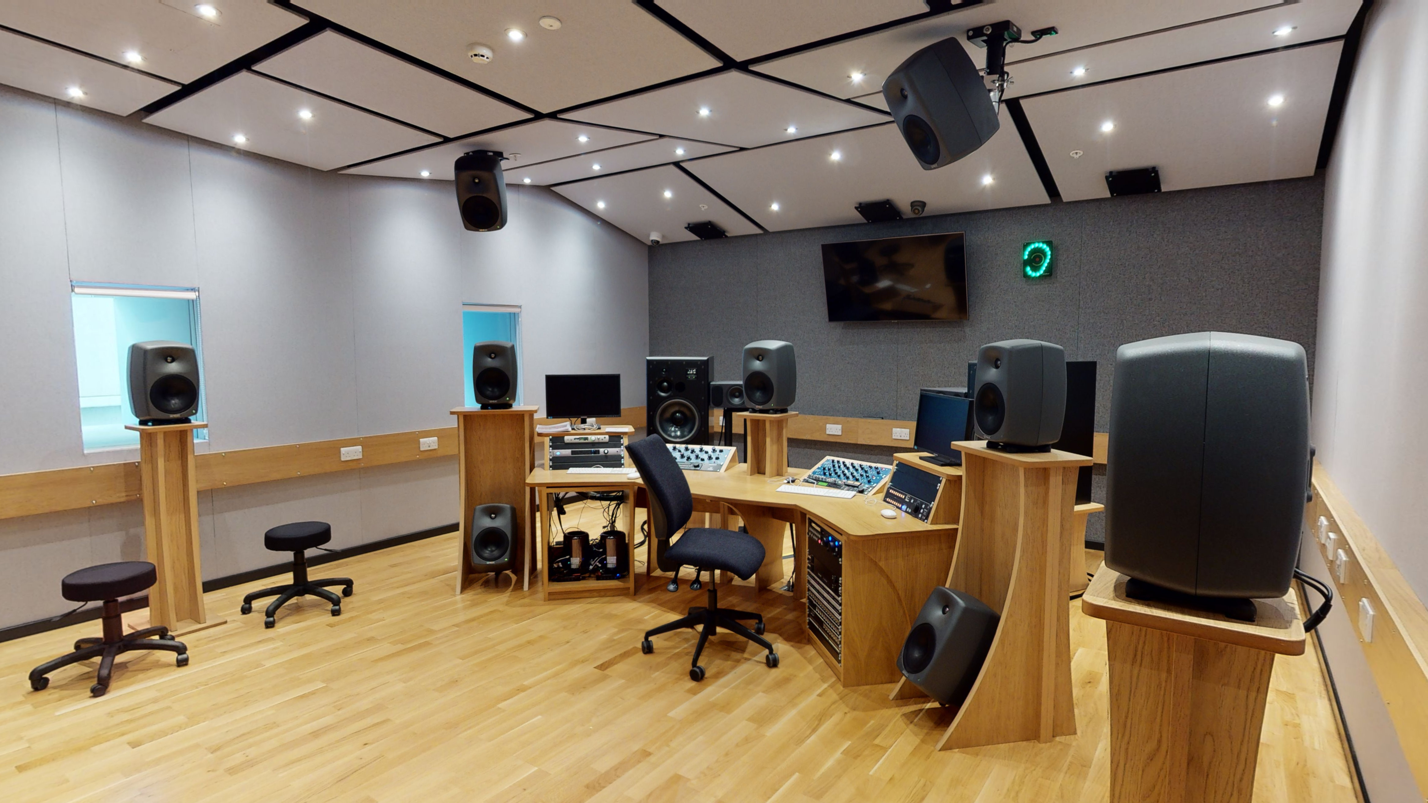 Central control desk in the centre of a music studio style space - surrounded by a circle of head height speakers.