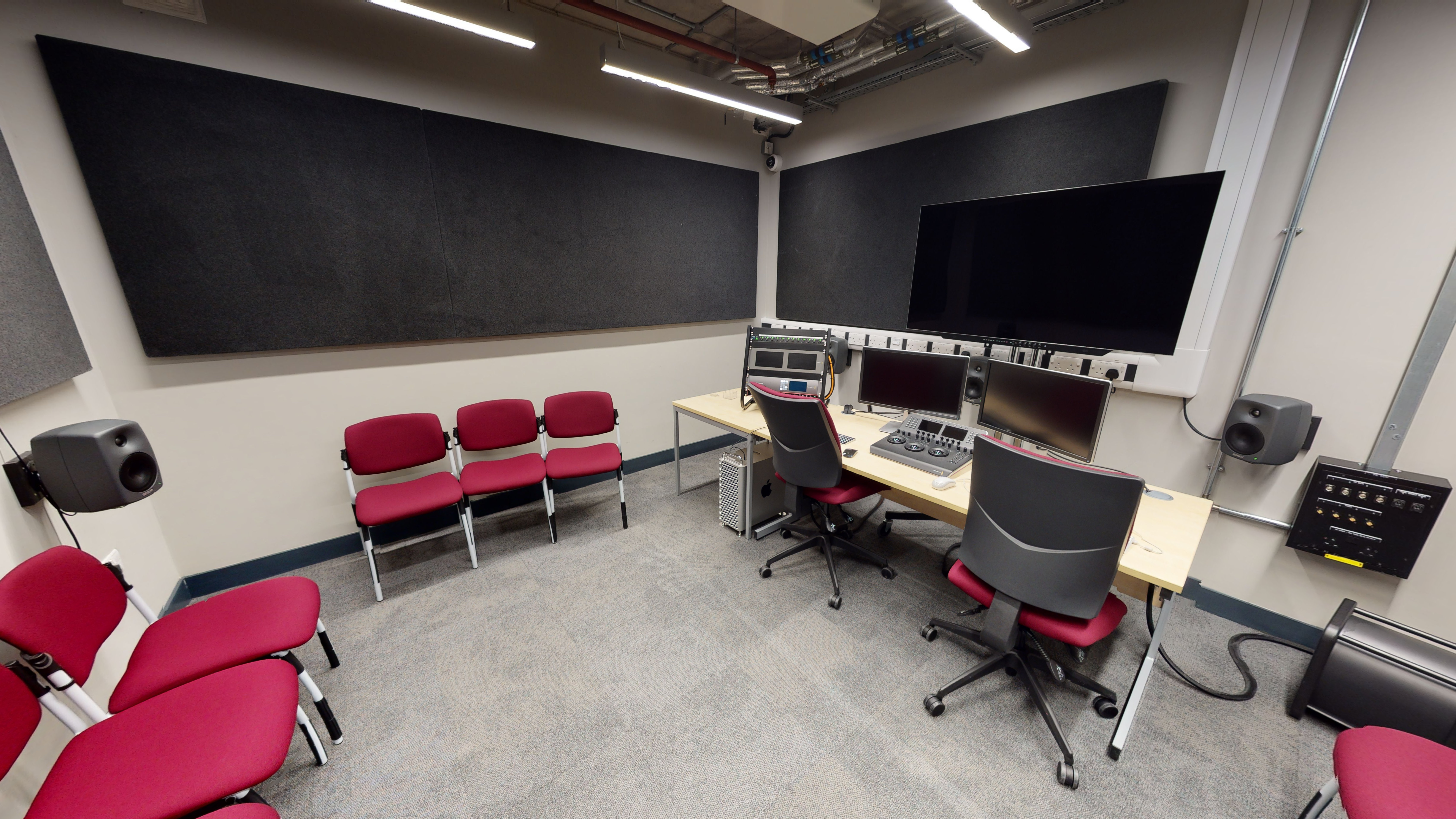 Desk with several large monitors and speakers with seating for a number of people.