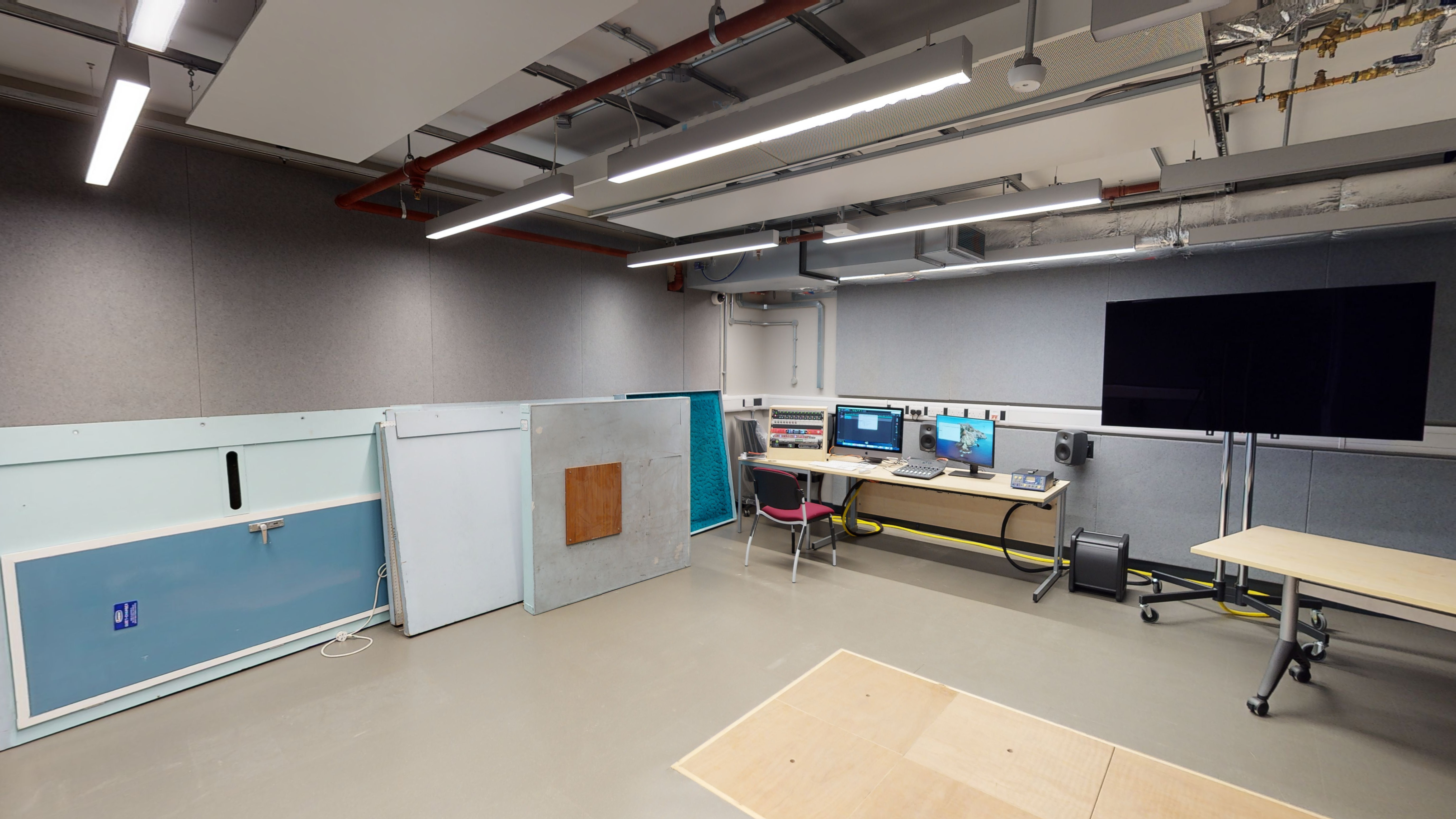Classroom style space with monitors, large screen, doors for making sound effects and covered over pit in the floor