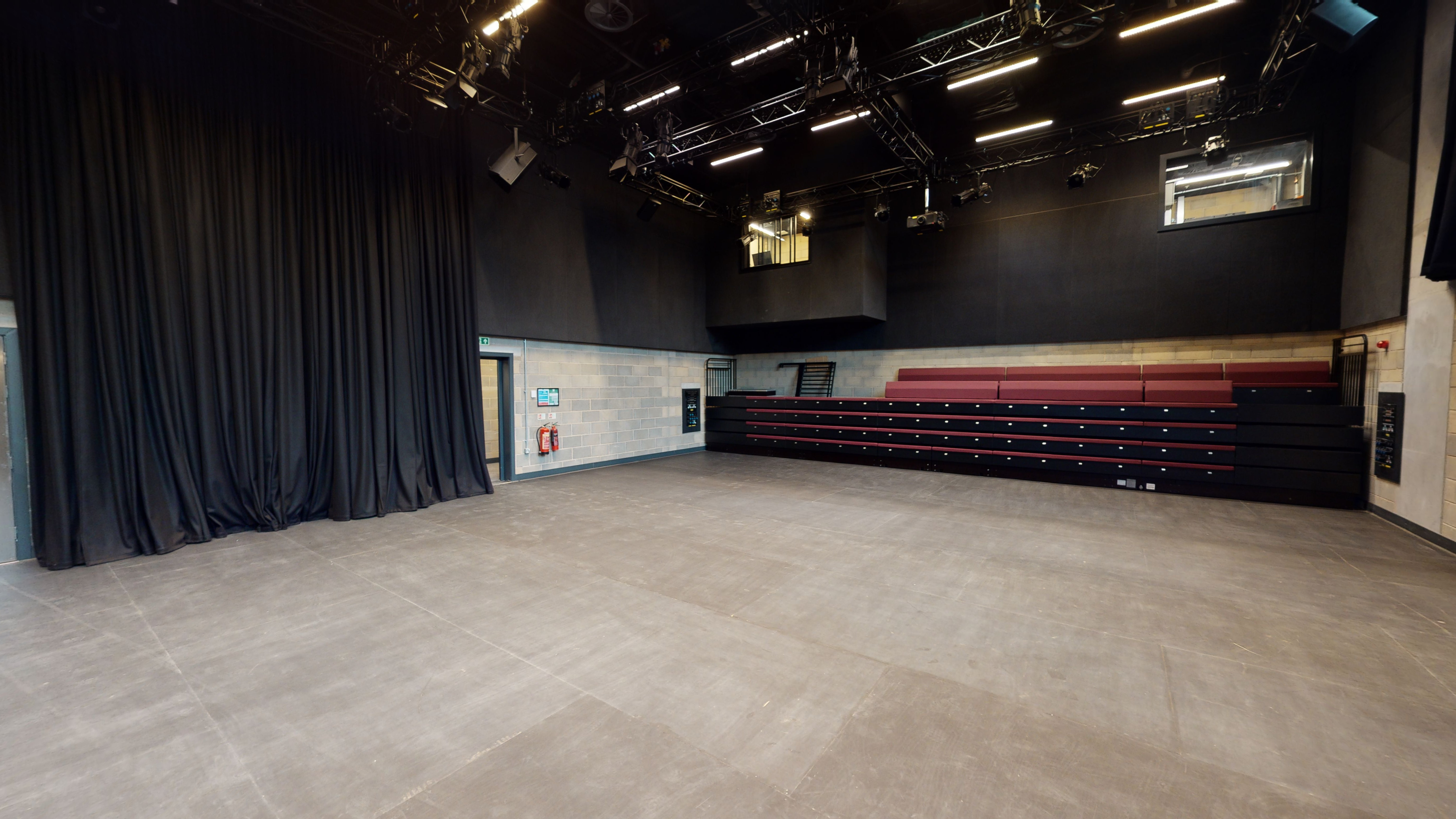 Medium sized theatre space with a bank of seating at the back.