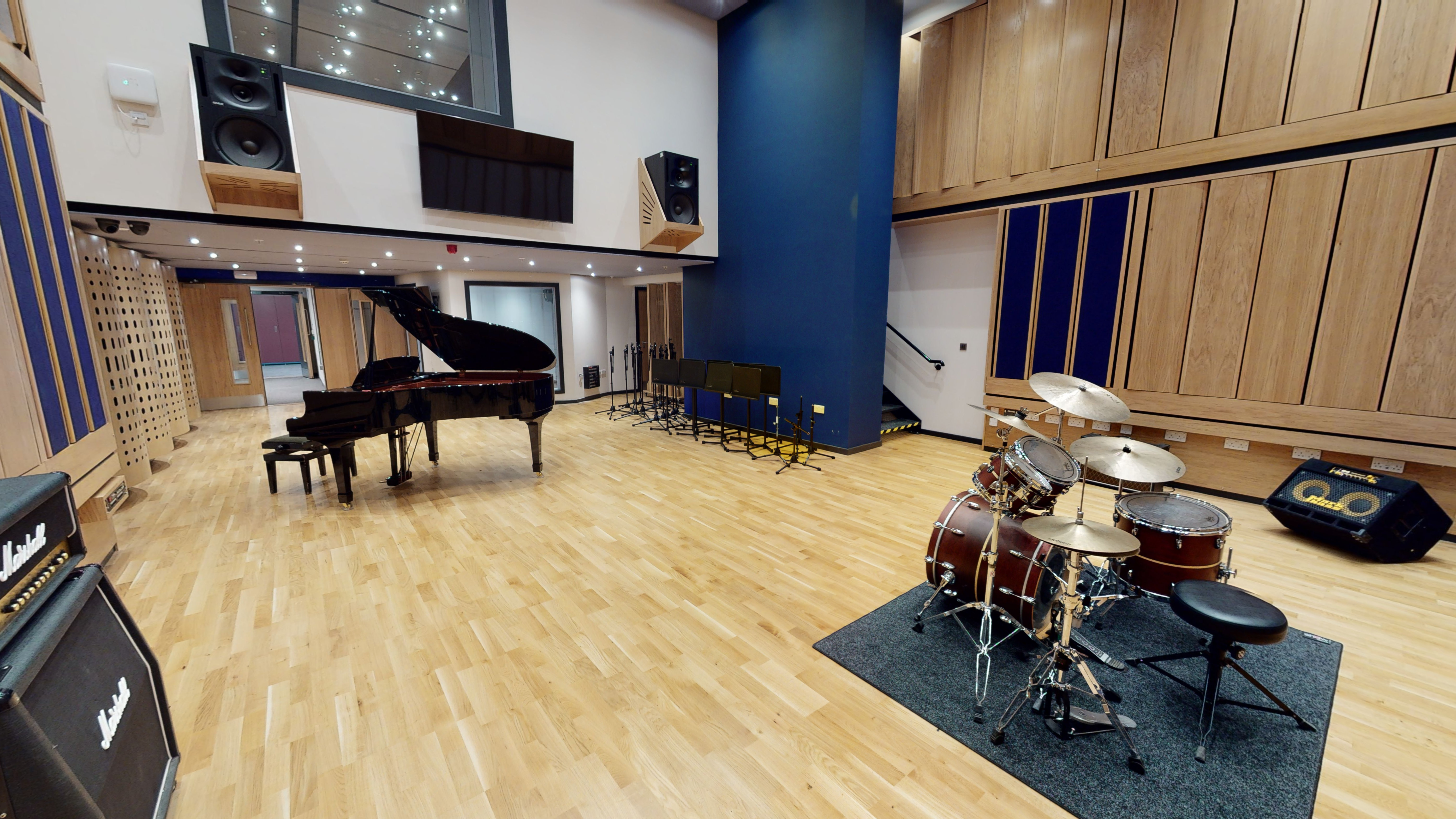 Large double height recording studio with a drum set and amp in foreground and a grand piano towards the back. Up above is a window from the control room.