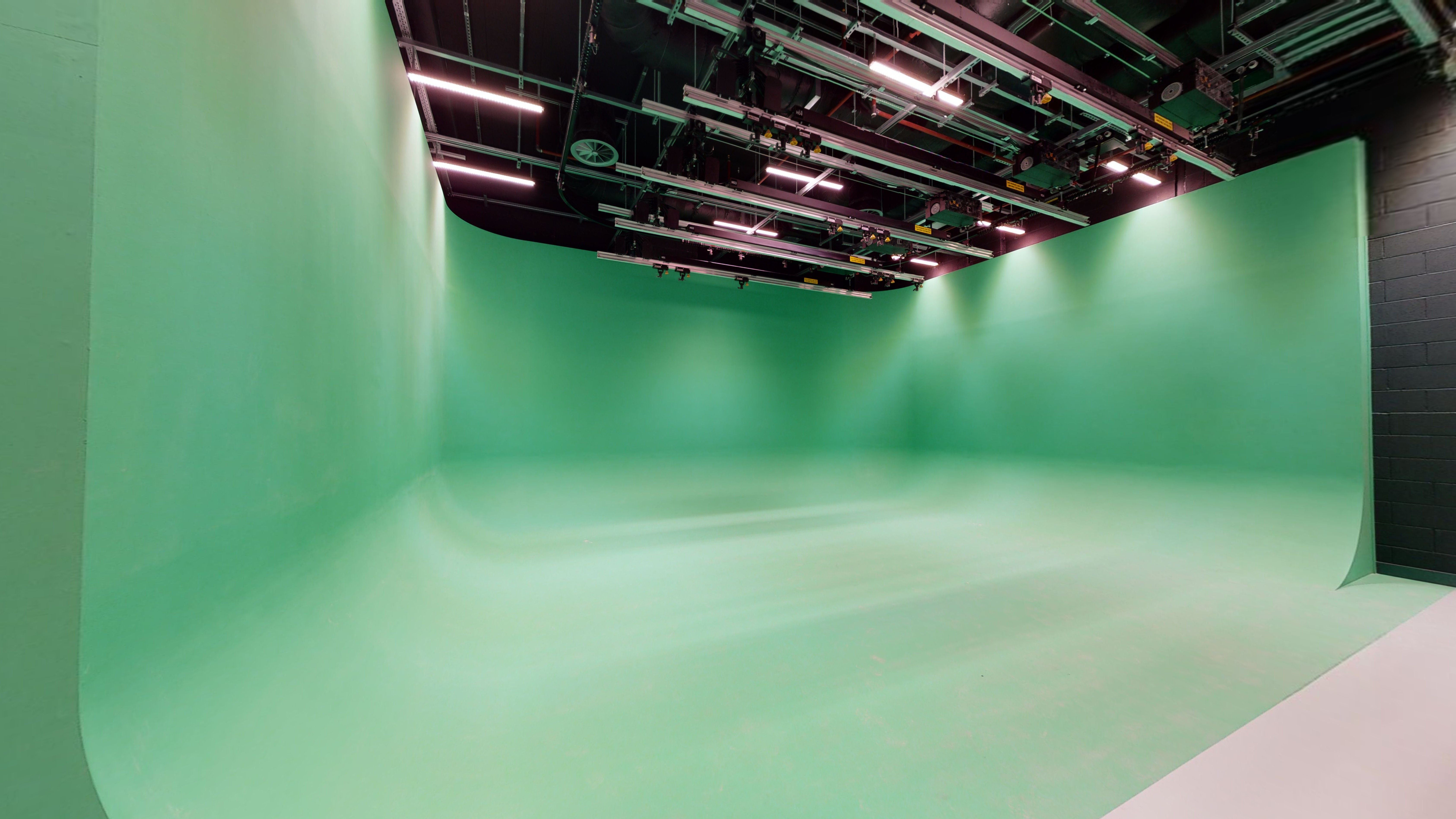 Film studio with a curved sided green screen on the floor and up 3 walls.