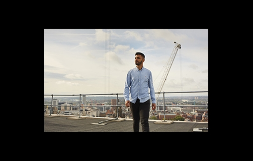 Man standing on a roof with a city scape and large crane behind him