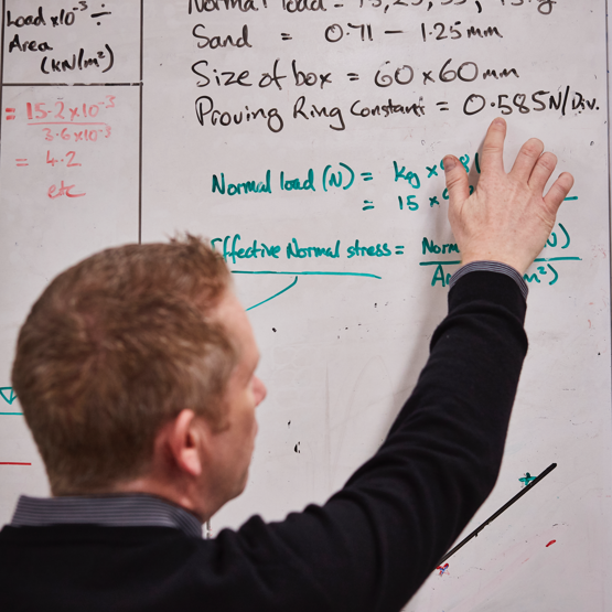 Man working out a formula on white board