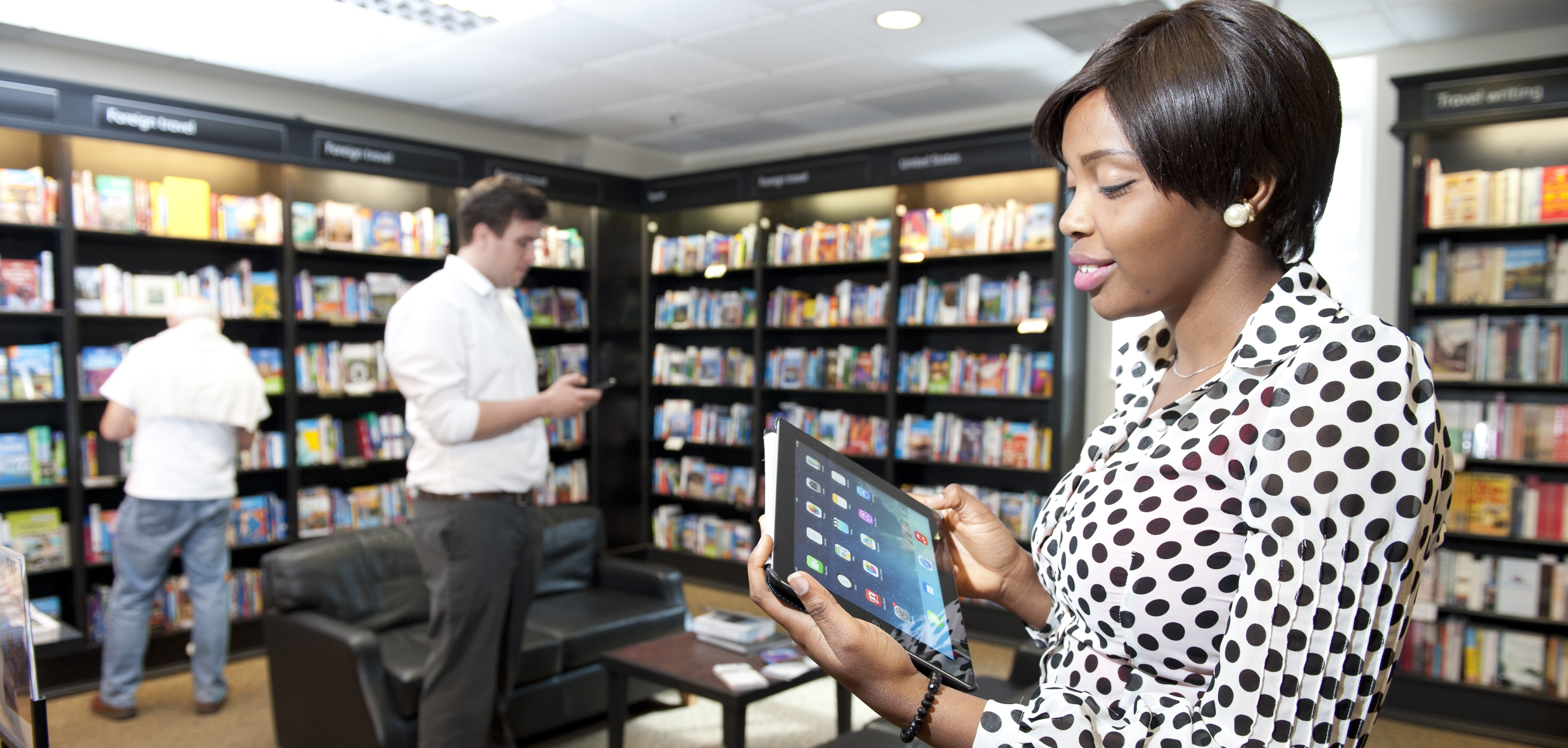 Women looking at tablet in bookshop